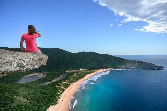 ženska sedi na skali nad plažo Lagoinha de Leste
