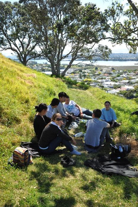 skupina mladih sedi na hribu nad Aucklandom