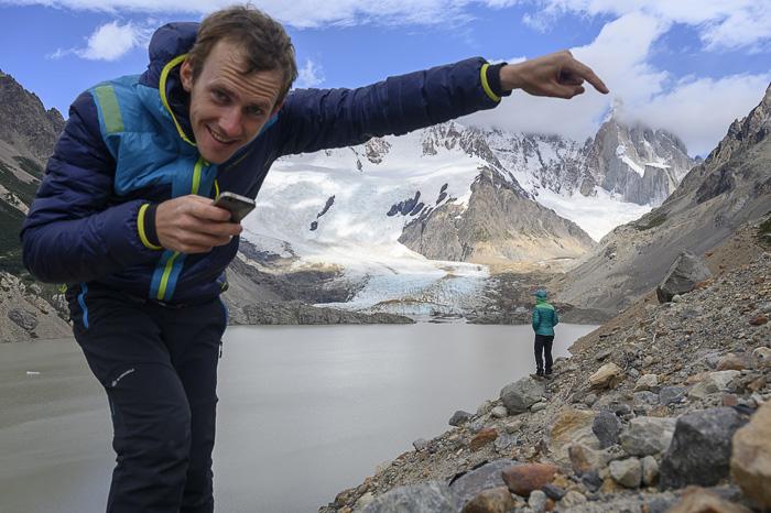 moški s telefonom v roki pod goro cerro torre