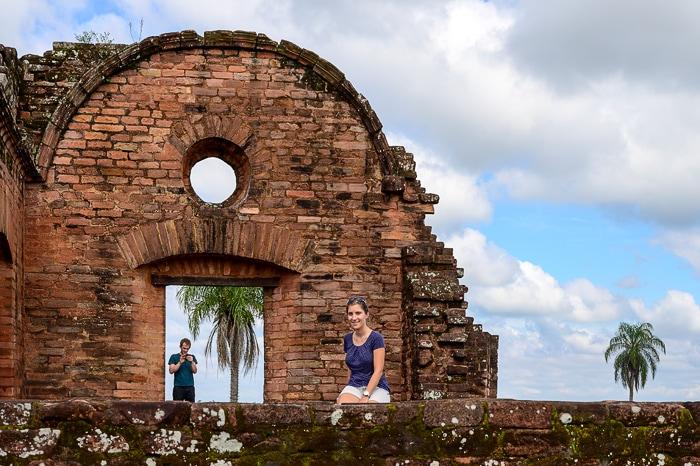 ženska sedi na kamnitem zidu pred ruševinami misijonov v Paragvaju