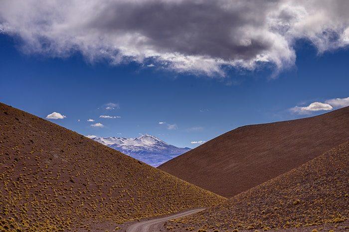 vijugasta cesta s pogledom na zasneženi vulkan