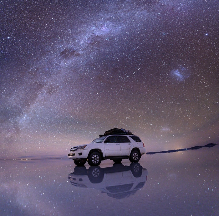 nočno nebo in pod njim avto v salar de uyuni