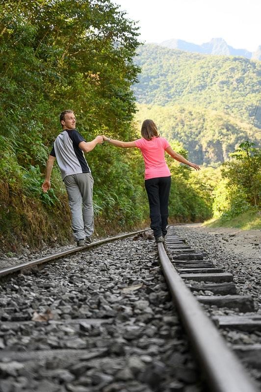 moški in ženska na železniških tirih na poti na machu picchu v lastni režiji