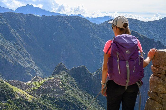 ženska z vijoličnim nahrbtnikom stoji pred machu picchu