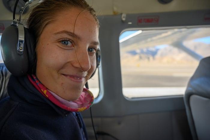 ženska na letalu s slušalkami