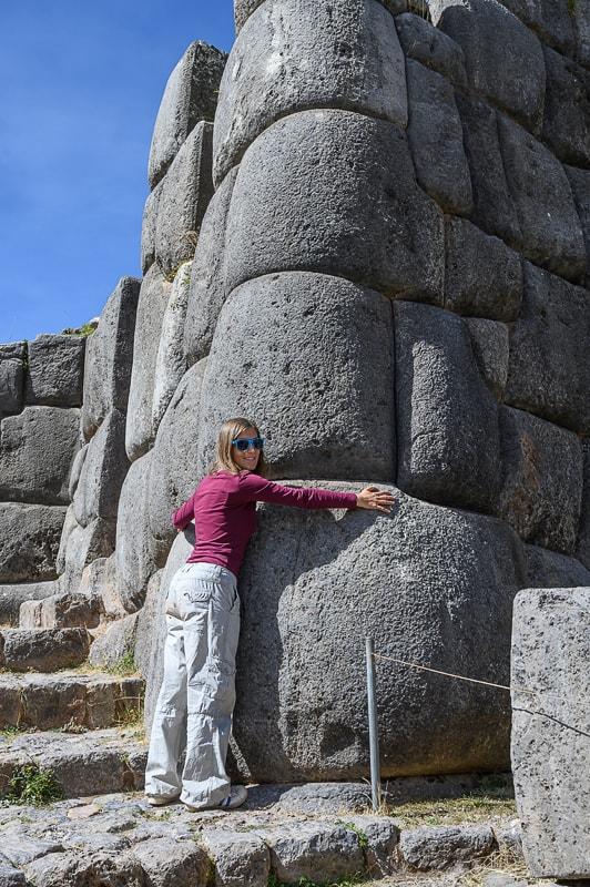 ženska pred ogromnimi zidaki v sacsaywaman