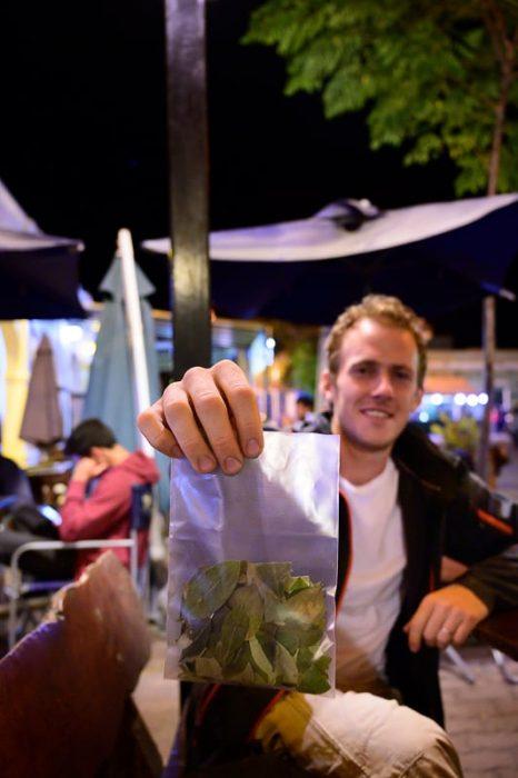 moški z vrečko kokinih listov