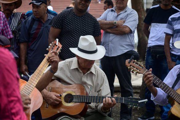 kolumbijski moški s klobukom igra na kitaro