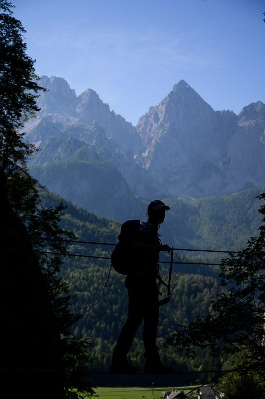 ženska prečka viseči most, v ozadju gora Špik