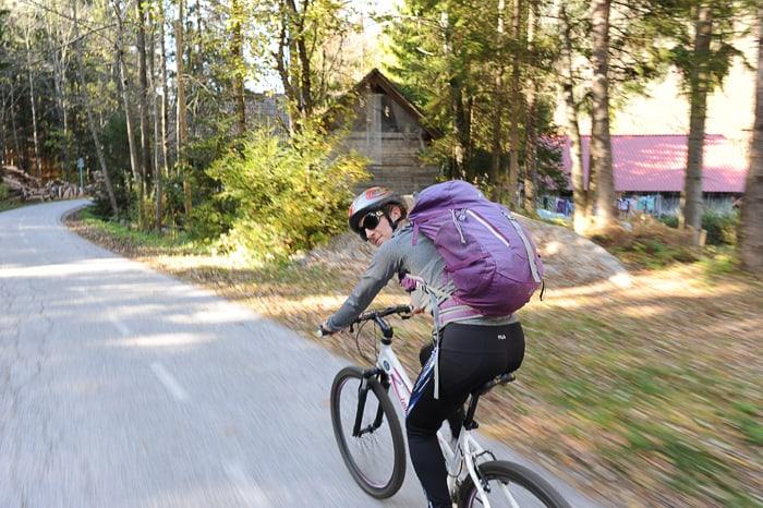 ženska z nahrbtnikom na kolesu. kolesarska pot kranjska gora D2