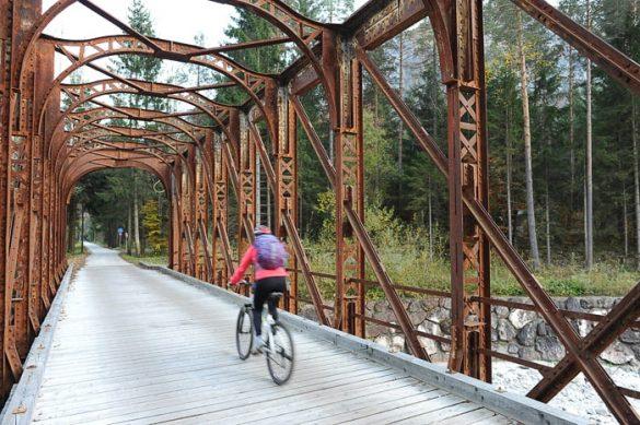 ženska na kolesu se pelje preko starega železniškega mostu