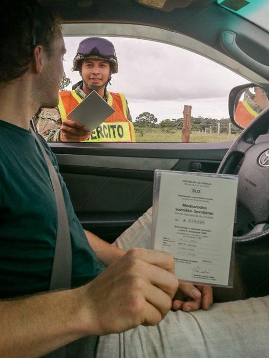 kolumbijski vojak pregleduje dokumente voznika. mednarodno vozniško dovoljenje v rokah