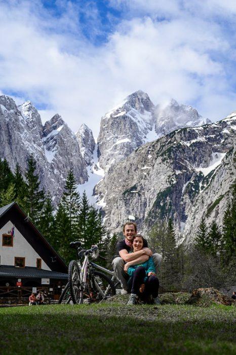 ženska in moški sedita na travi pred kočo v Tamarju. V ozadju gora Jalovec