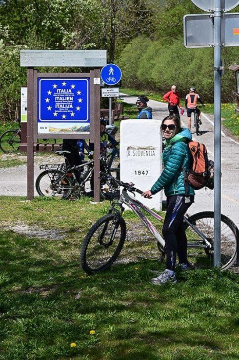 ženska s kolesom pred mejo italija-slovenija