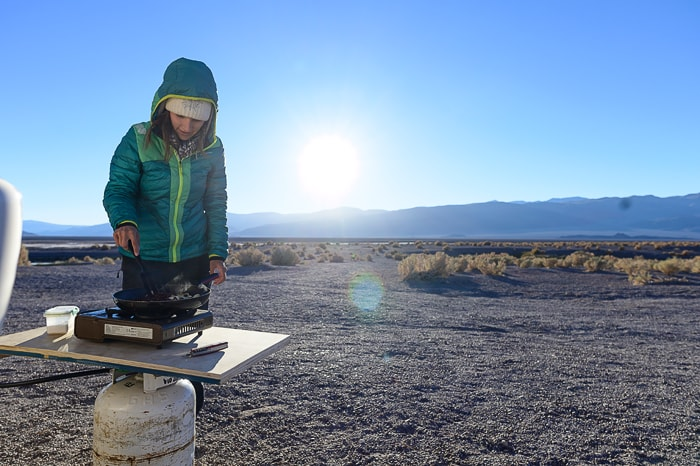 ženska kuha kosilo na prenosnem kuhalniku. Puna, Argentina