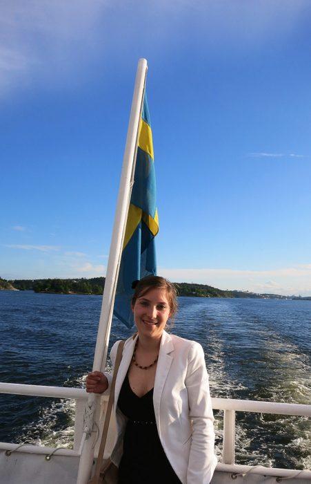 ženska na ladji ob švedski zastavi