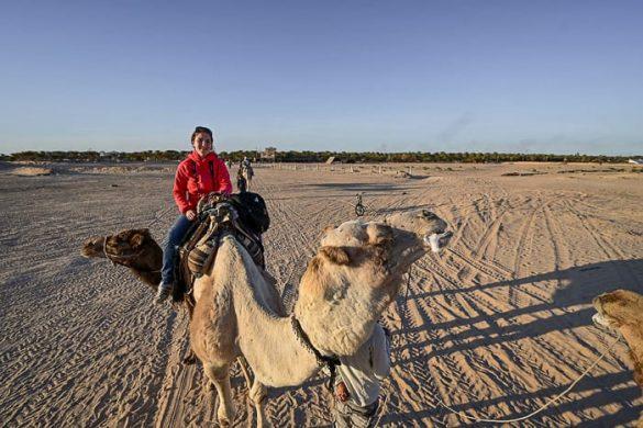 ženska na kameljem hrbtu v Sahari