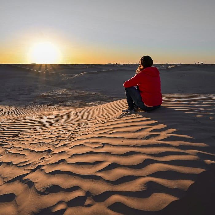 ženska opazuje sončni zahod v Sahari, Tunizija