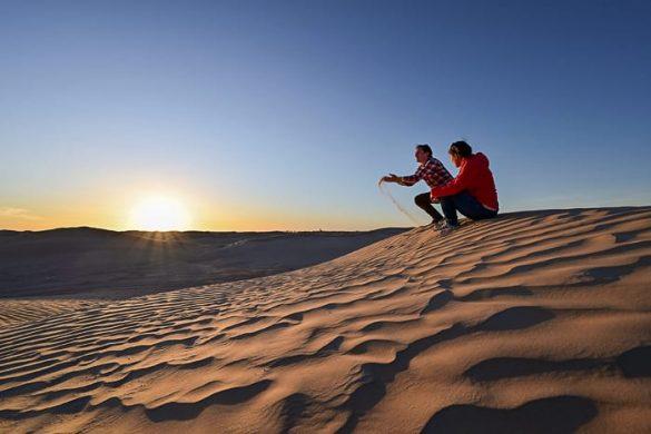 Moški in ženska ob sončnem zahodu v Sahari