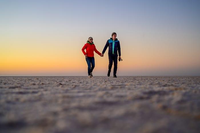 moški in ženska hodita po posušenem slanem jezeru, Chott el Jerid, Tunizija