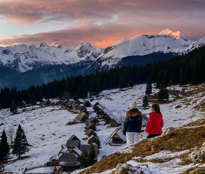 dve postavi opazujeta sončni zahod na planini Zajamniki. Pokljuka.