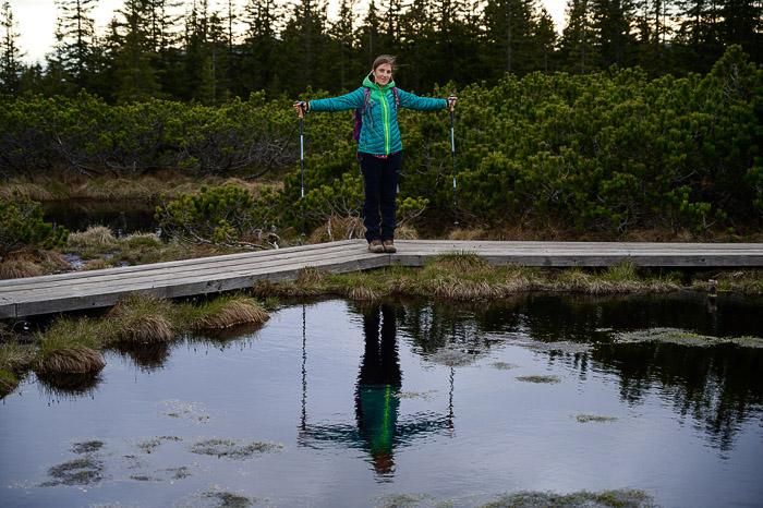 ženska stoji ob črnem jezeru. v jezeru je odsev ženske