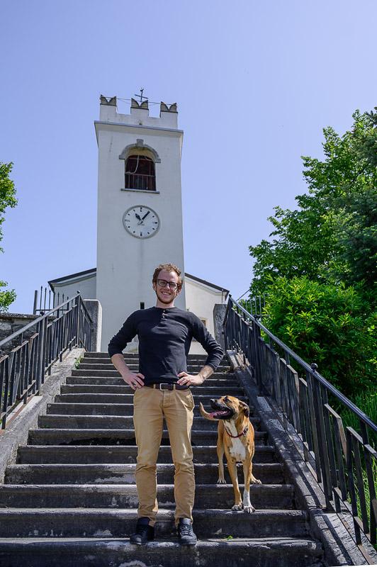 moški in pes na stopnicah pred cerkvijo