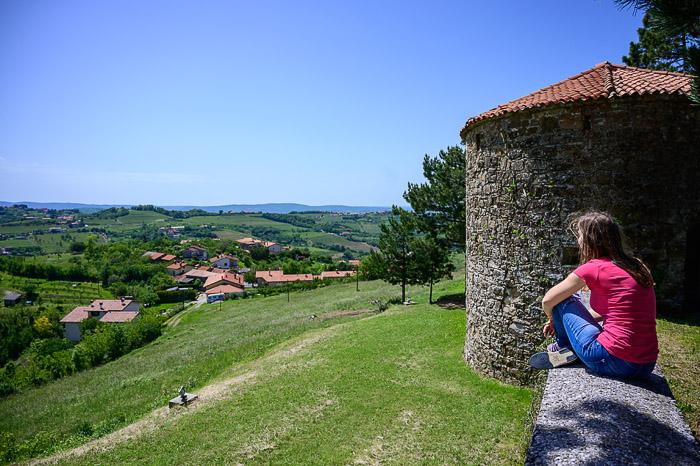 ženska sedi na srednjeveškem obzidju. V ozadju okrogel obrambni stolp