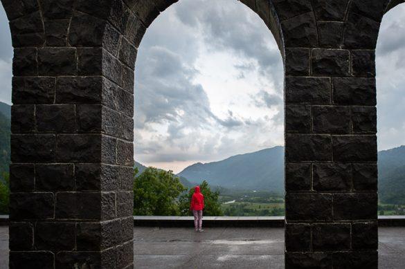 ženska v rdeči jakni stoji med obokom. Kostnica Kobarid