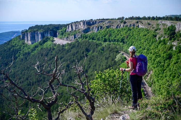 ženska stoji na robu pečine Kraški rob
