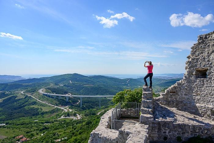 ženska stoji na ruševinah črnokalskega gradu, v ozadju viadukt, hribi in morje