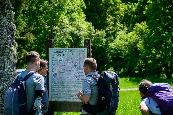 skupina pohodnikov preučuje zemljevid roške pešpoti