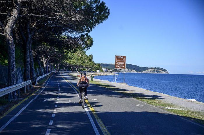 ženska na kolesu se pelje ob morju proti Izoli