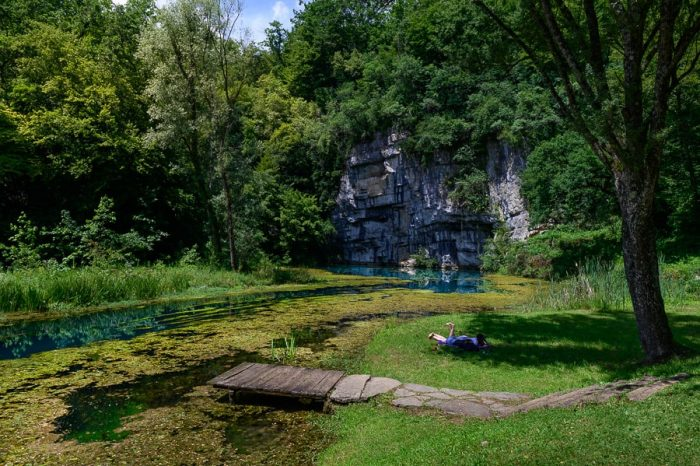 izvir Krupe: zelen travnik iz katerega gre lesen most proti reki.
