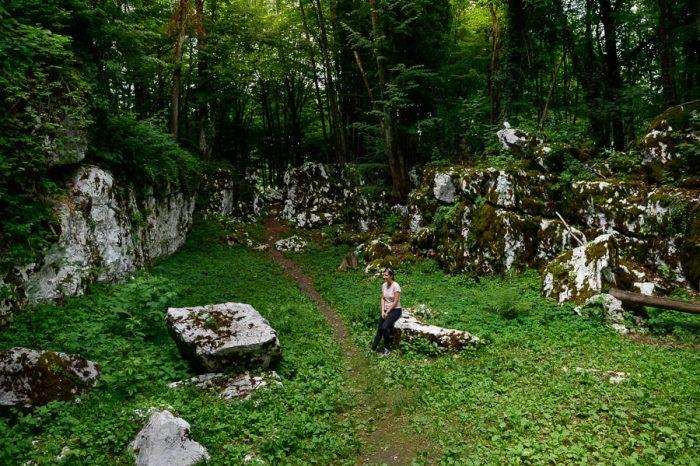 ženska sedi na skali sredi mitreja - starodavnega svetišča
