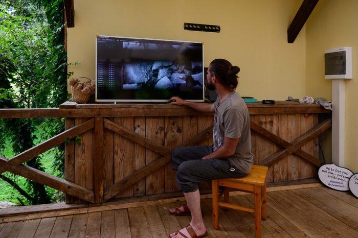 moški sedi ob televiziji in spremlja, kje se skriva črna človeška ribica