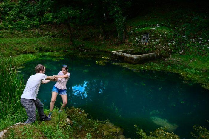 moški in ženska se držita za roke nad modrim jezerom - izvir Okno, Bela krajina