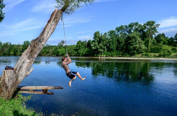 moški skače v vodo s pomočjo gugalnice. kopališče Benetič pri Vinici