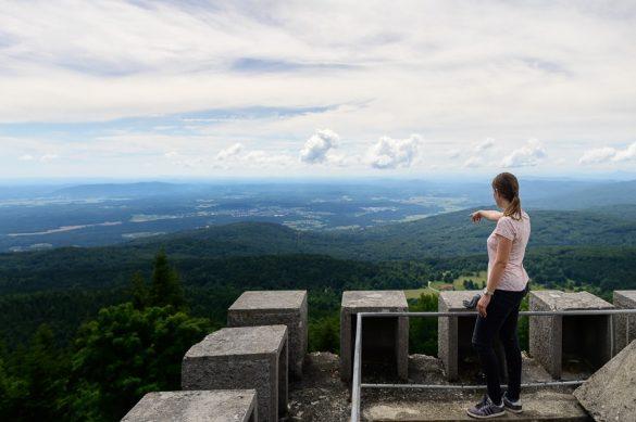 ženska na razglednem stolpu kaže na razgled v dolini