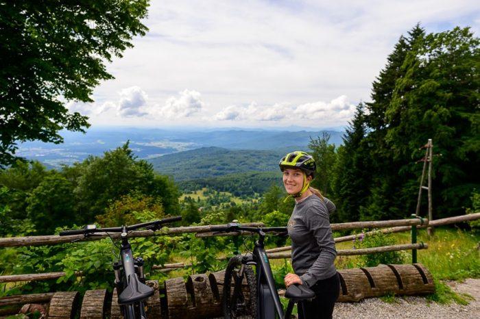 ženska ob kolesu, zadaj razgled na dolino pod Mirno goro