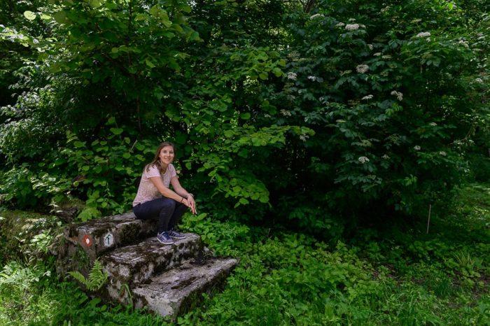 ženska sedi na stopnicah - ostanek nekdanje kočevarske hiše