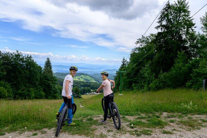 moški in ženska sedita na kolesu na robu travnika