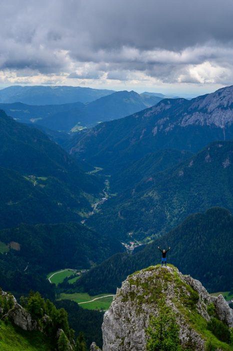 moški na skali, spodaj dolina poraščena z gozdom