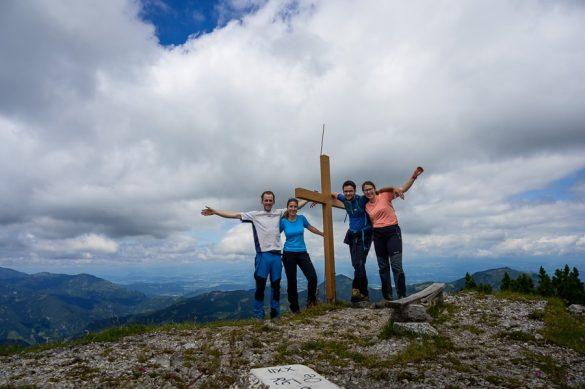 skupina pohodnikov stoji na vrhu Olševe, ob križu