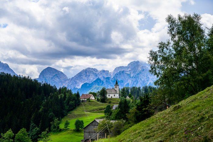 cerkvica na hribu, v ozadju gore