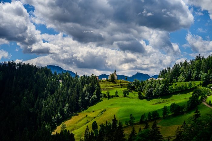 cerkvica na zelenem griču z dramatičnimi oblaki na nebu