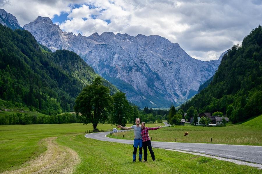 moški in ženska na travniku pred logarsko dolino. v ozadju gore ter drevo lipa
