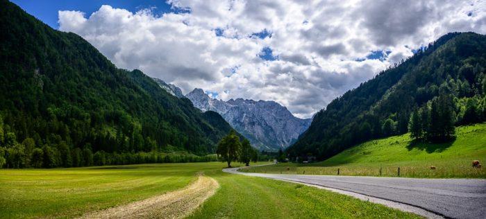 vstop v Logarsko dolino: cesta, zeleni travniki, na koncu doline pa visoke gore