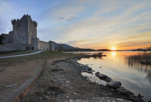 grad ob jezeru in zahajajoče sonce v ozadju