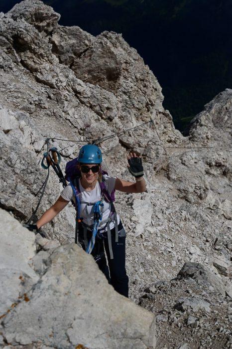 ženska s čelado in opremo za plezanje na ferati